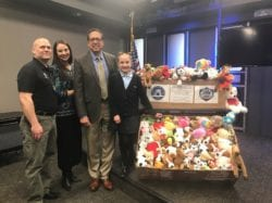 Academy personnel standing next to a large basket of stuffed animals
