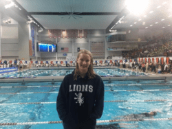 Emily Vanderlee standing in front of a long lap pool