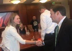 Liz Burch shaking hands in a meeting