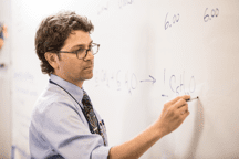 Male teacher at white board writing science equation