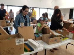 Volunteers fill boxes with school supplies