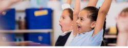 Young girls raising hands in class