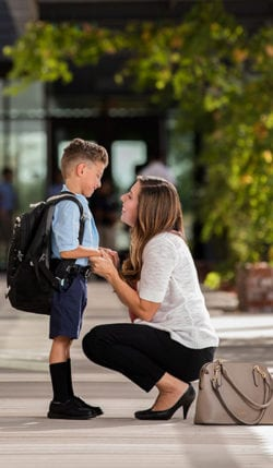 Mom says goodbye to her son on the first day of school.