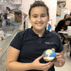 Great Hearts student holds holiday ornament