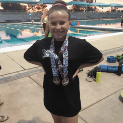girl standing outside of swimming pool wearing medals