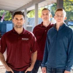 3 veritas prep alumni standing on porch