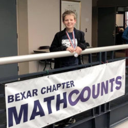student standing near Math Counts banner
