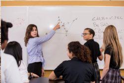 female teacher with math problem on white board
