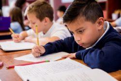 young boy doing class work