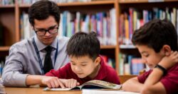male teacher with young boy reading