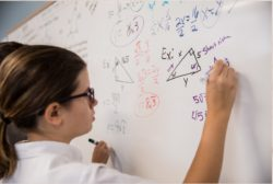 girl at whiteboard doing math